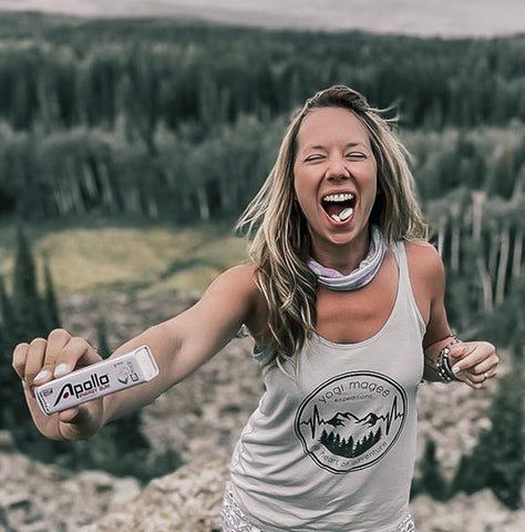 woman on mountain holding a pack of Apollo Energy Gum with piece in mouth