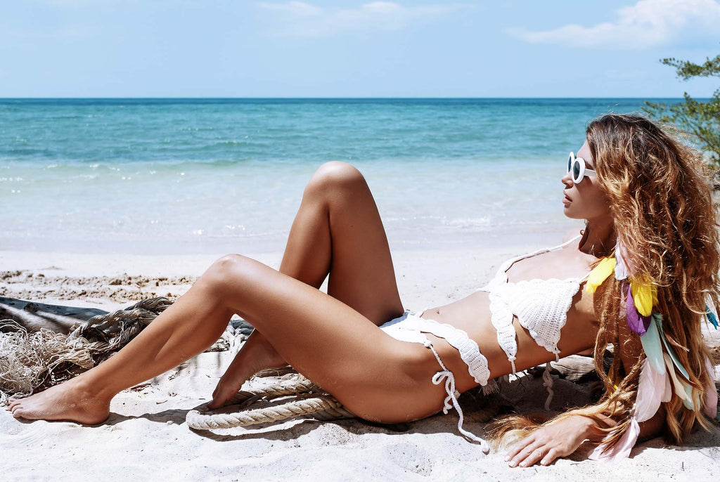 Airbrush tanned influencer at photoshoot on the beach | Sol Potion Sunless Tanning | Best Spray Tan Solutions and Skincare