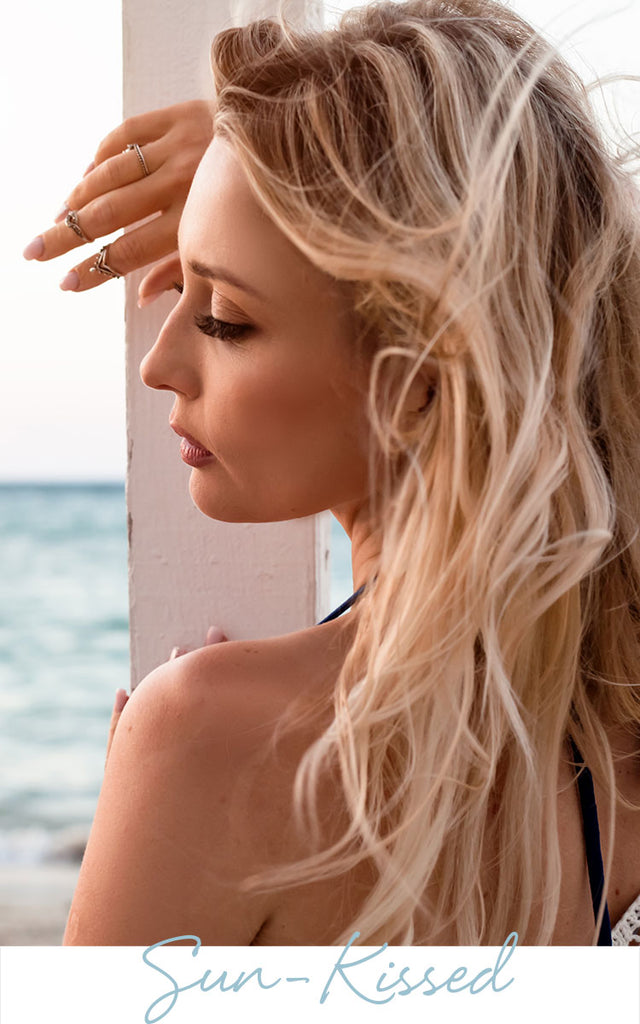 Sun-kiss blonde woman by the water | Sol Potion Sunless Tanning | Best Spray Tan Solutions and Skincare