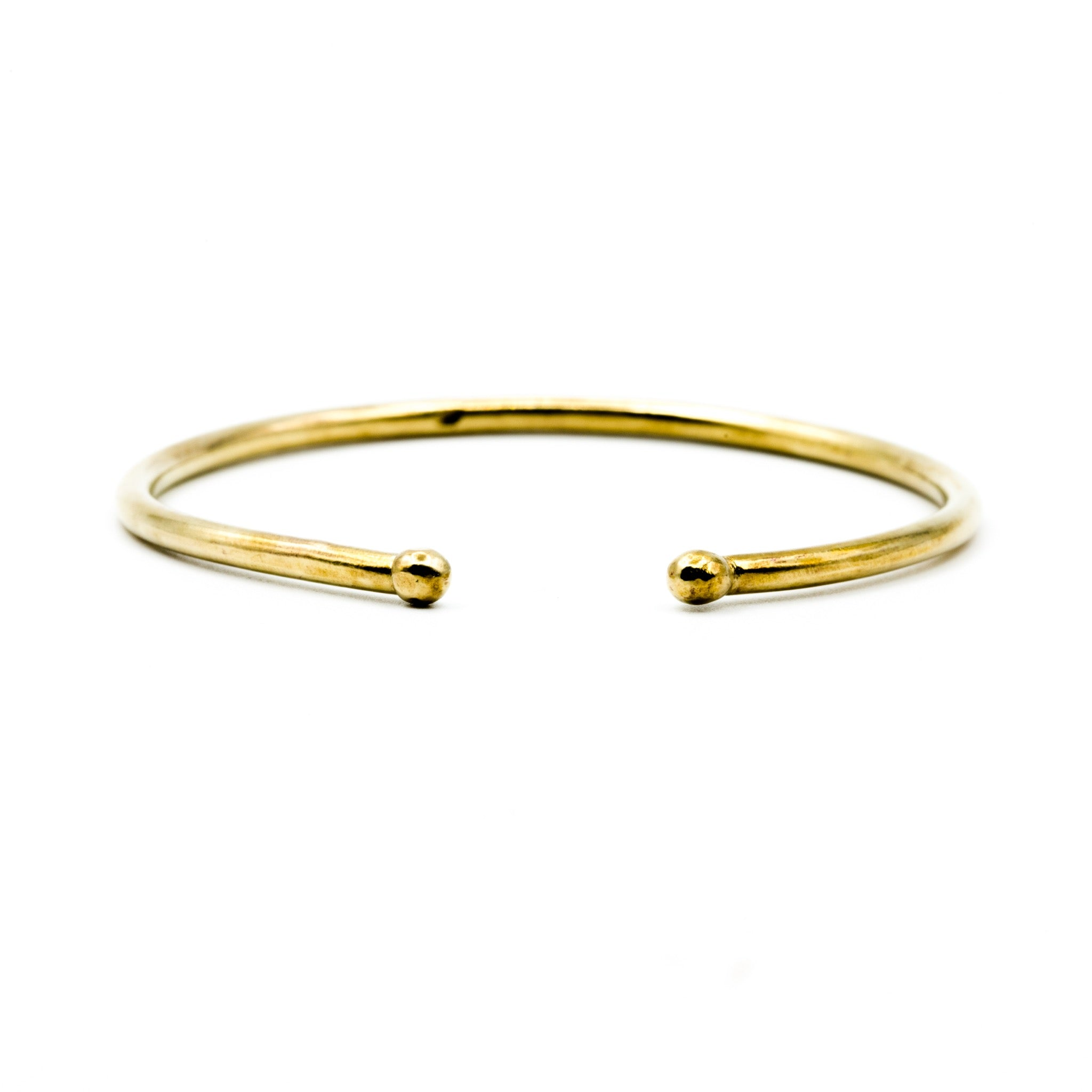brass cuff with balled ends on white background
