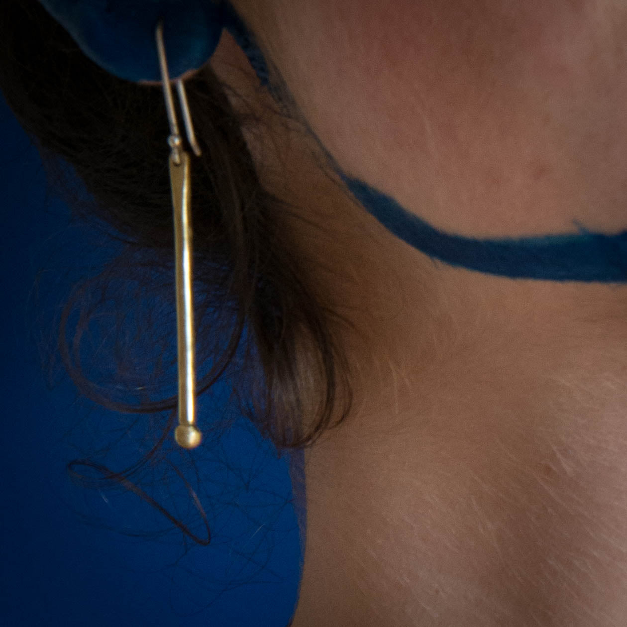model using long brass balled earrings