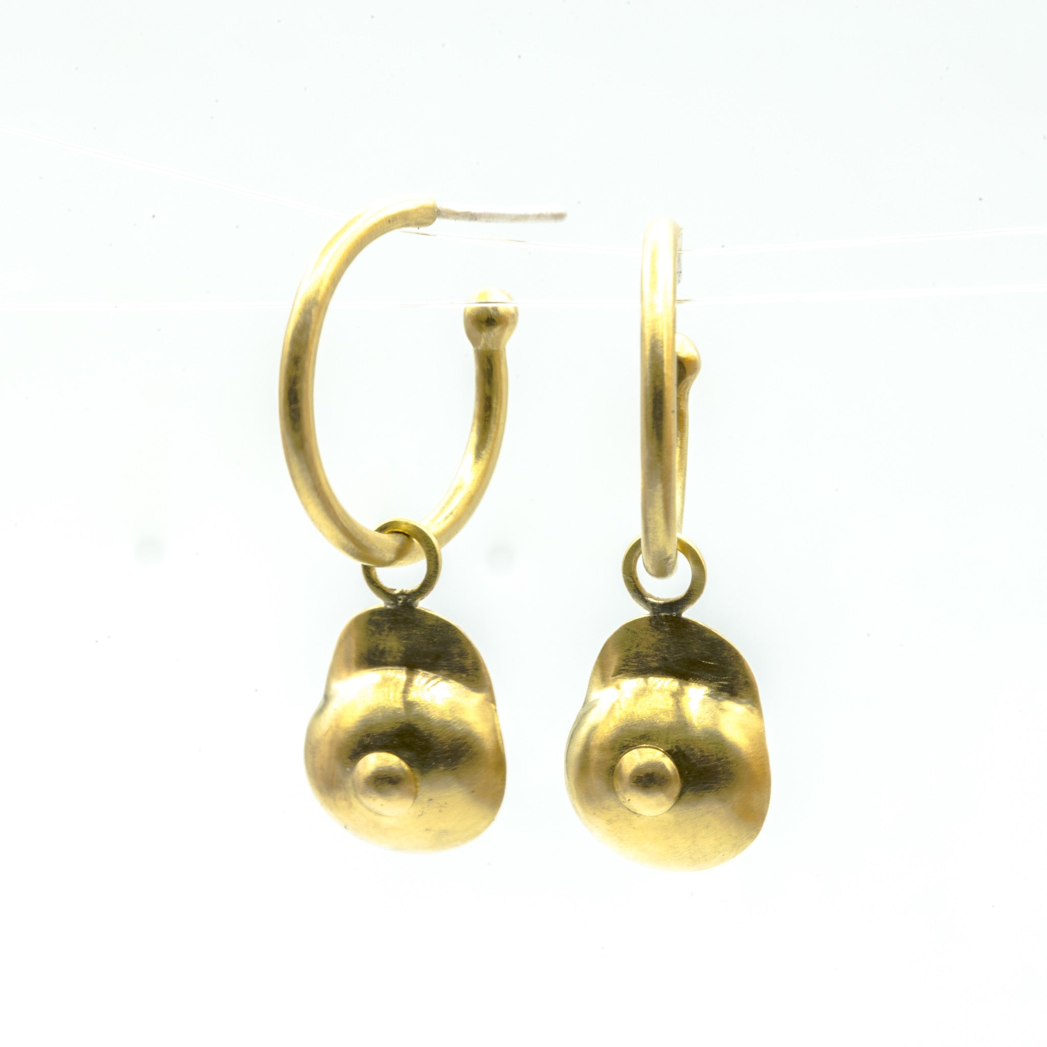 boobie shaped brass dangly hoops on white background