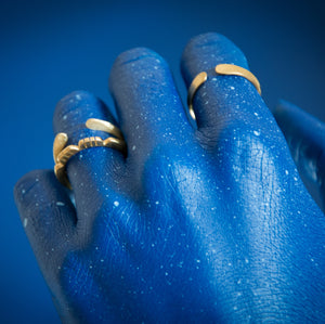 blue painted hand on blue background with brass rings