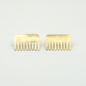 brass comb shaped earrings on white background
