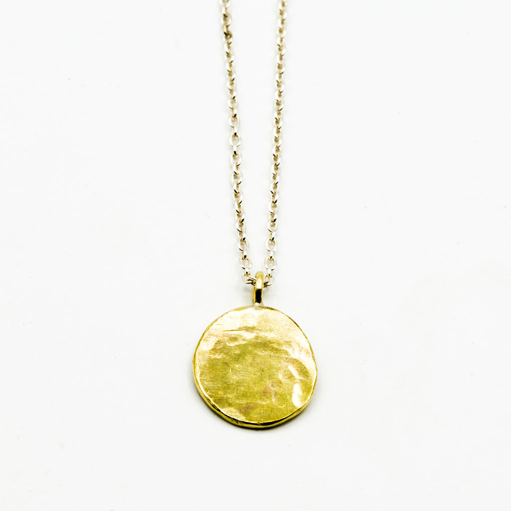 Brass circle pendant with sterling silver chain on white background