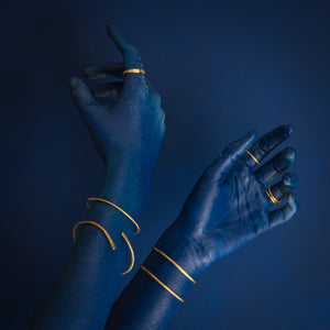blue hands on blue background wearing brass rings and cuffs