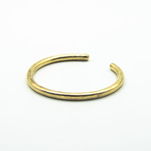 thick brass cuff back view on white background