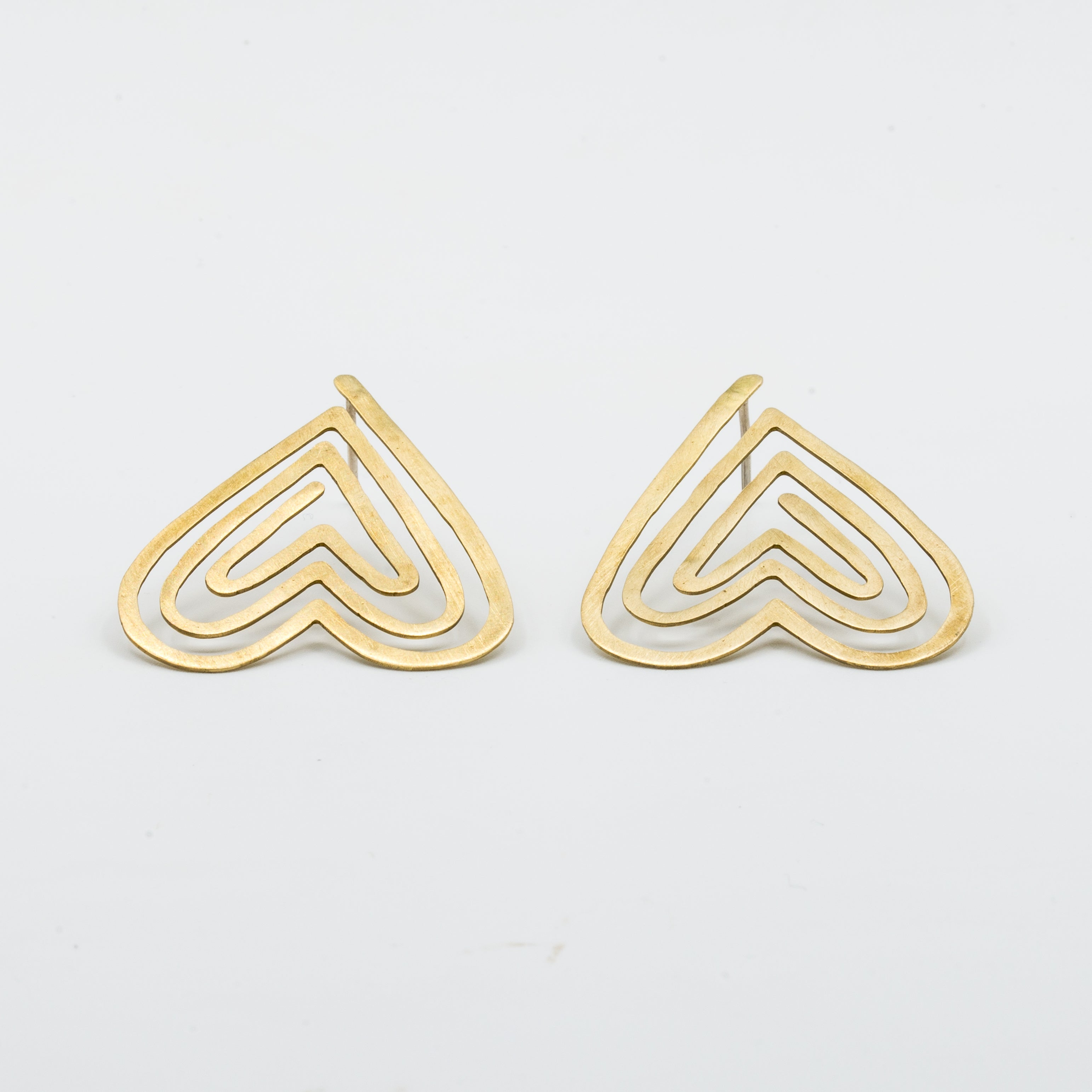 angled view heart shaped stud earrings on white background