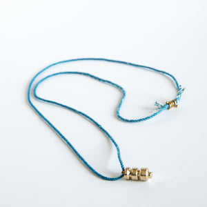 Sculpted brass pendant on this blue silk rope