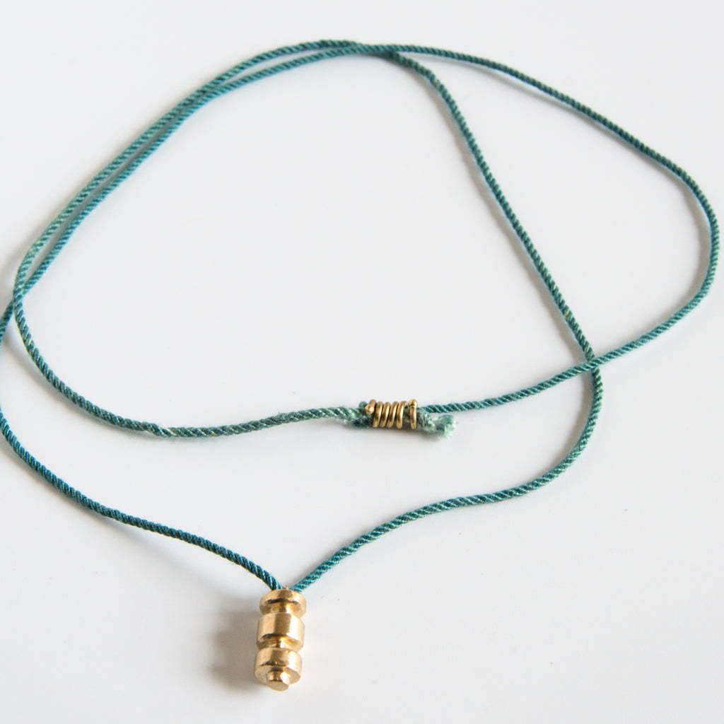 Sculpted brass pendant on this green silk rope