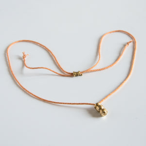 Sculpted brass pendant on this orange silk rope