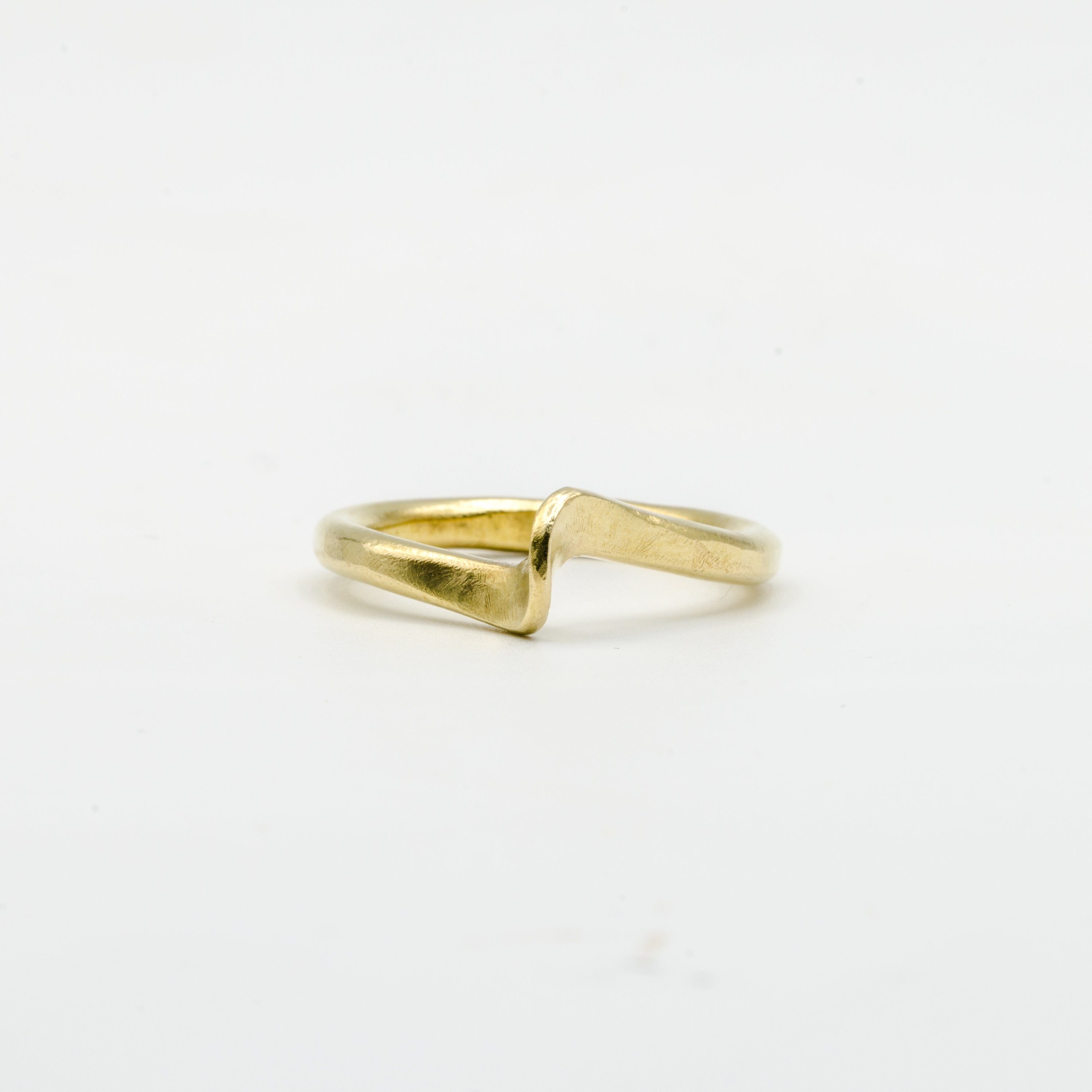 hand forged curved brass ring on white background
