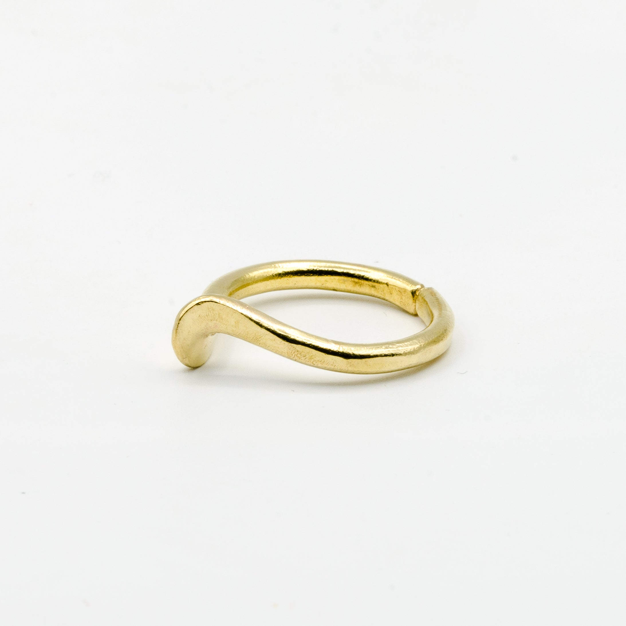 side view of hand forged curved brass ring on white background