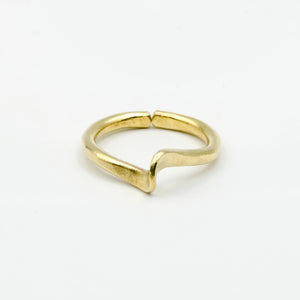 top view of hand forged curved brass ring on white background