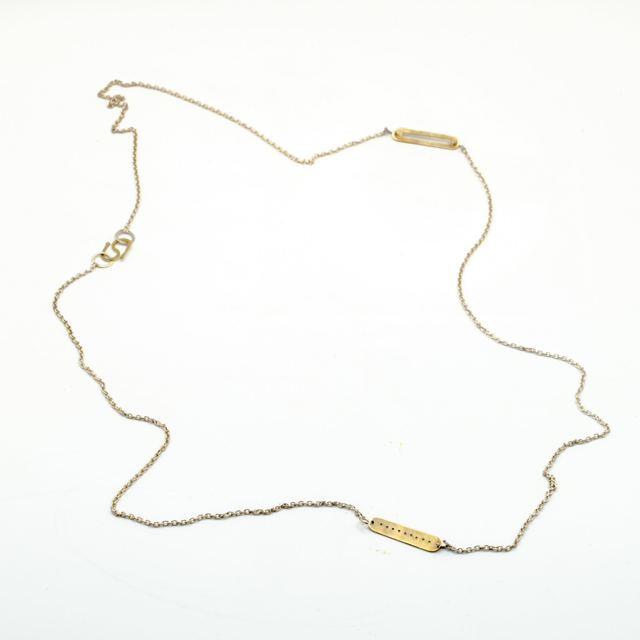 top view of brass cutout pieces on silver chain necklace