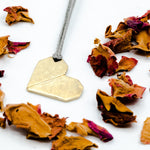 origami heart brass pendant with rose petals close up