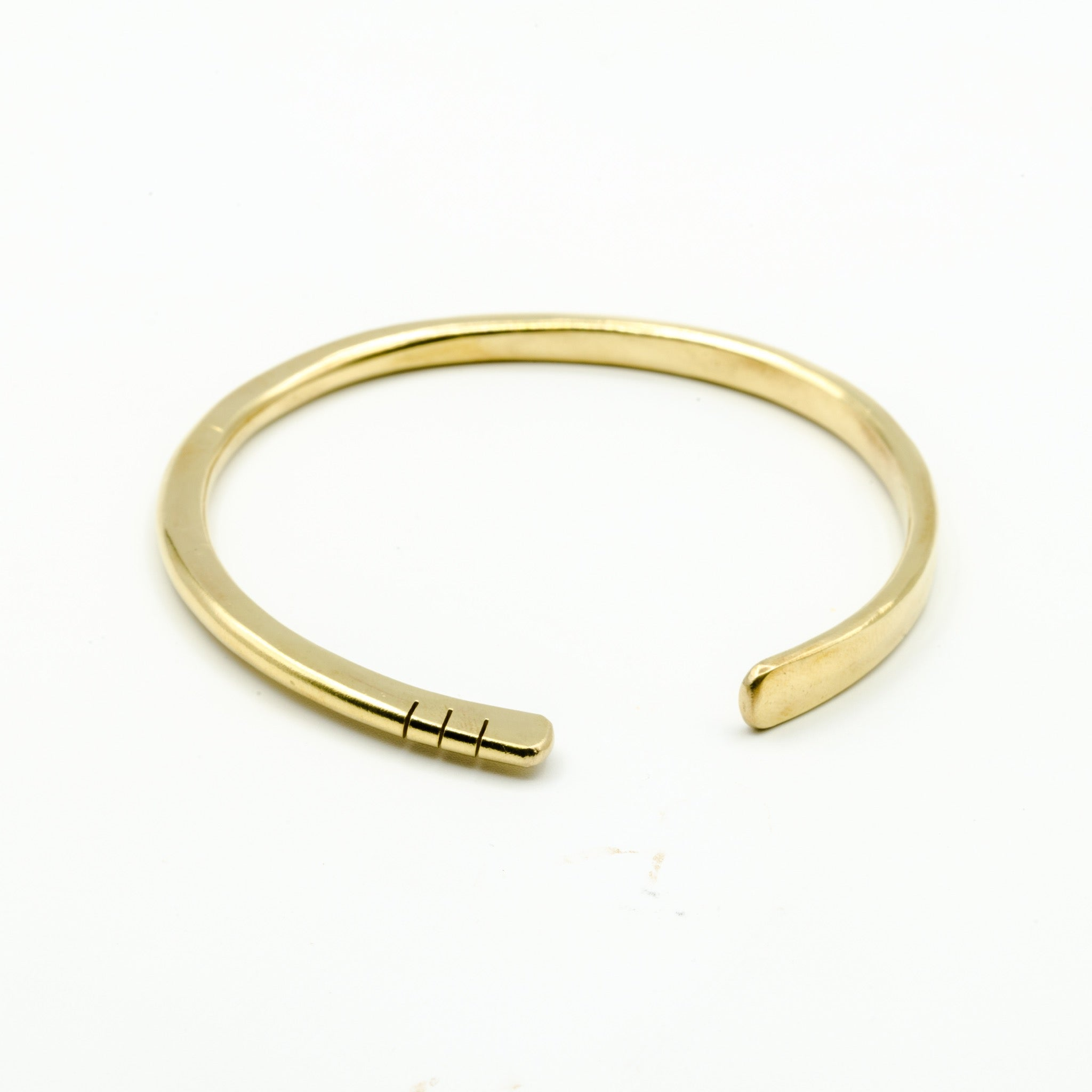 hand forged brass bangle with three cut notches on white background