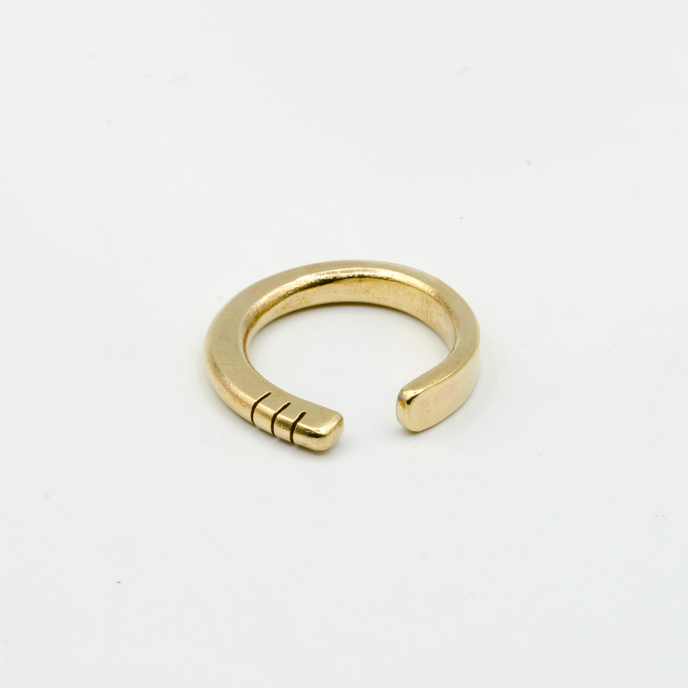 top view of hand forged brass ring with three notches