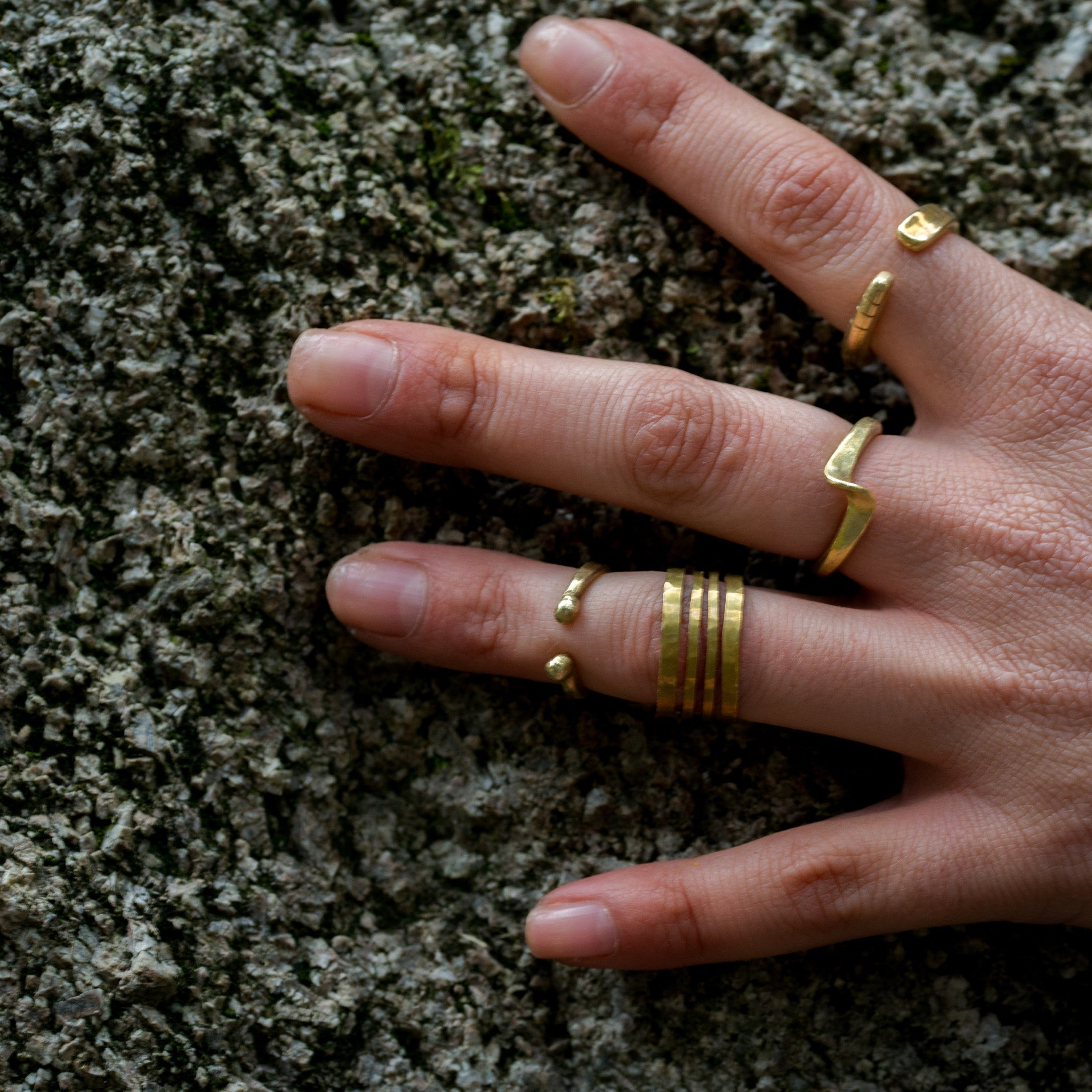 model wearing hand forged curved brass ring
