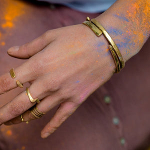 model wearing hand forged brass bangle with three cut notches and rings