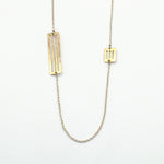 silver chain with brass cutout pieces necklace on white background