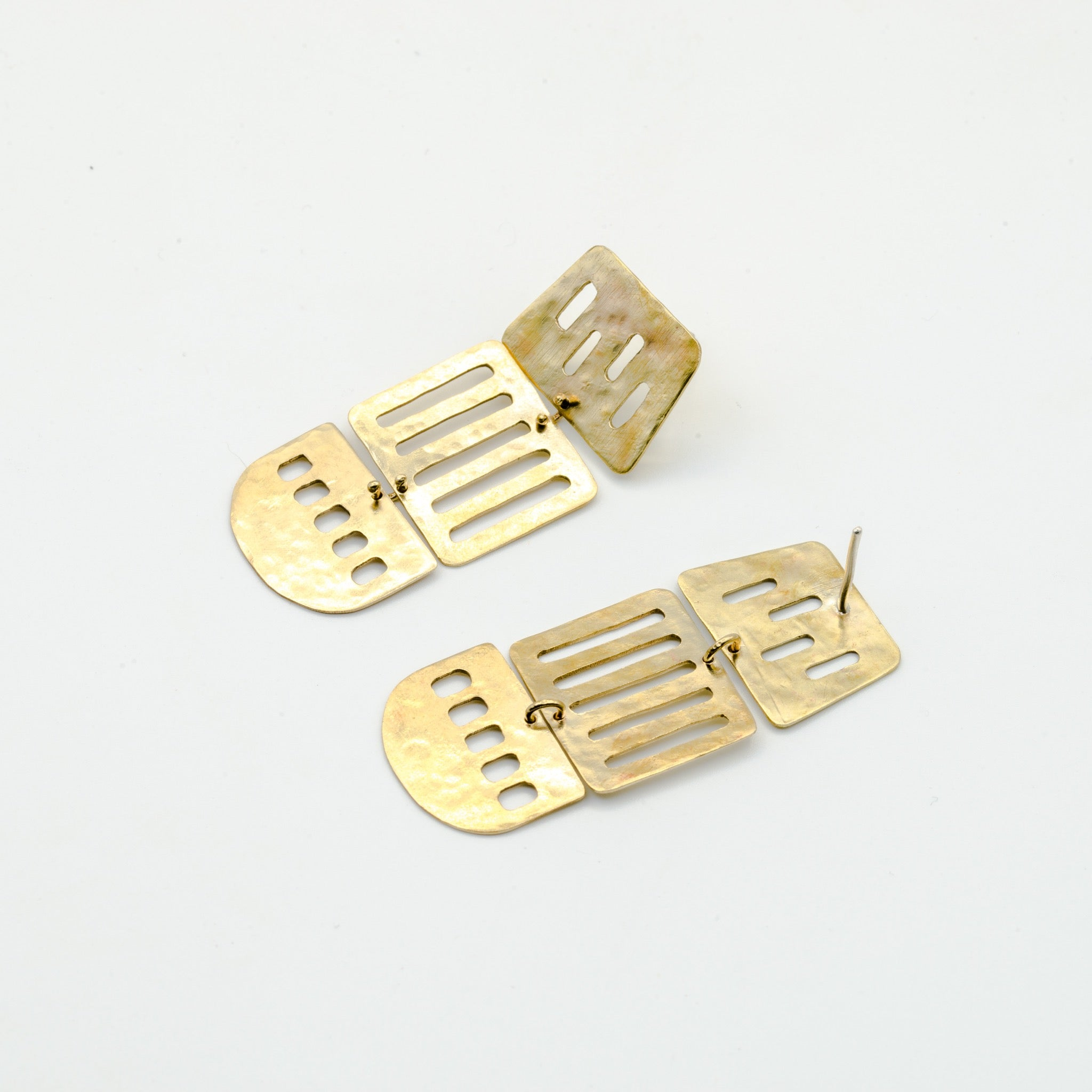 long brass cutout earrings on white background