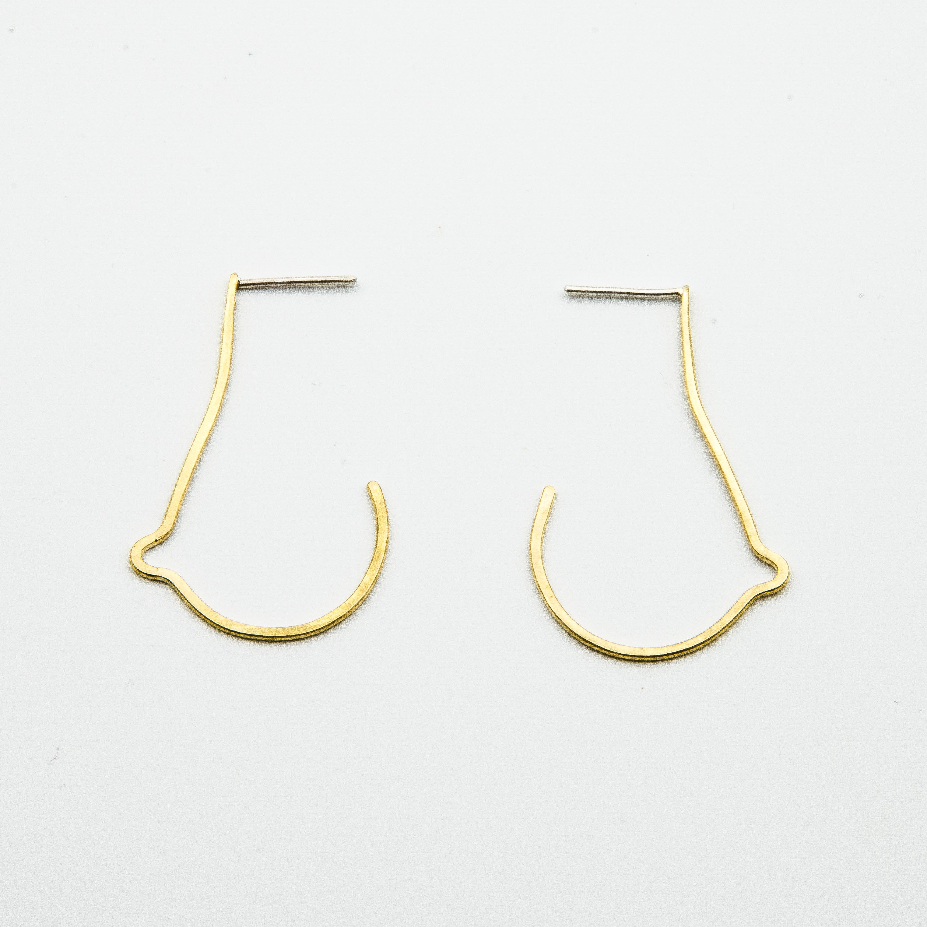 breast shaped brass wire earrings on white background