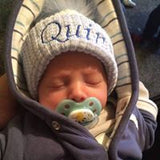 baby boy in personalised blue hat with fur pom