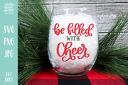 "Glass filled with white snow, handwritten text on glass ""be filled with Cheer"""