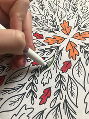 woman coloring with markers on Fall coloring page
