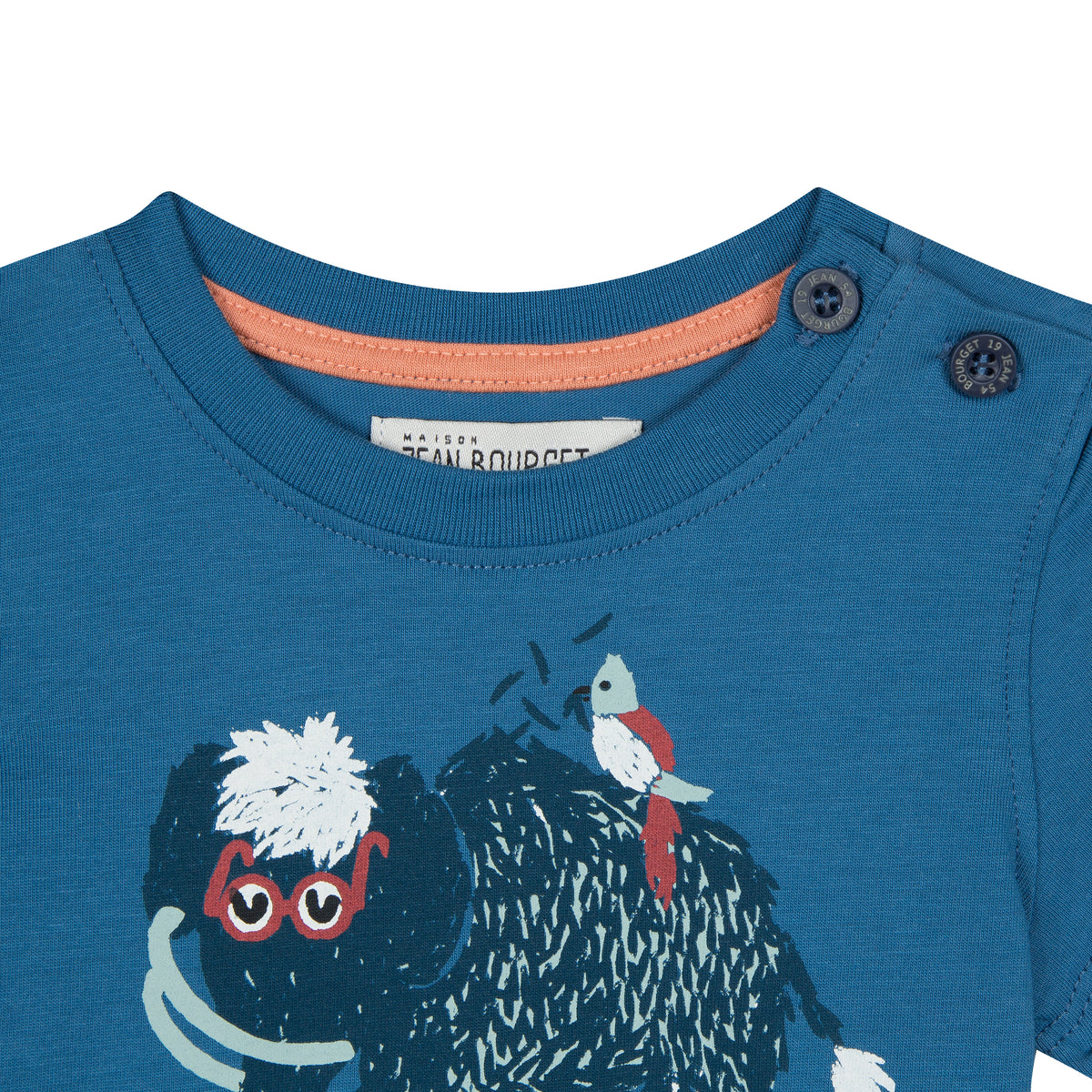 Blue cotton jersey t-shirt printed with a mammoth adorned with glasses on the front. Two buttons placed on the left shoulder. By Jean Bourget.