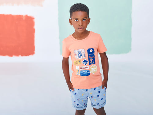 Jean Bourget light blue chambray bermuda shorts are embroidered with yellow camels and blue and orange palm trees all over.