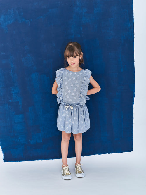 Jean Bourget light blue chambray dress is adorned with silver lurex bees in all over. The silhouette is animated with bands fluttering on the sides at the front and in the back. The skirt is pleated and the waist is bent by an elastic decorated with a golden bow.