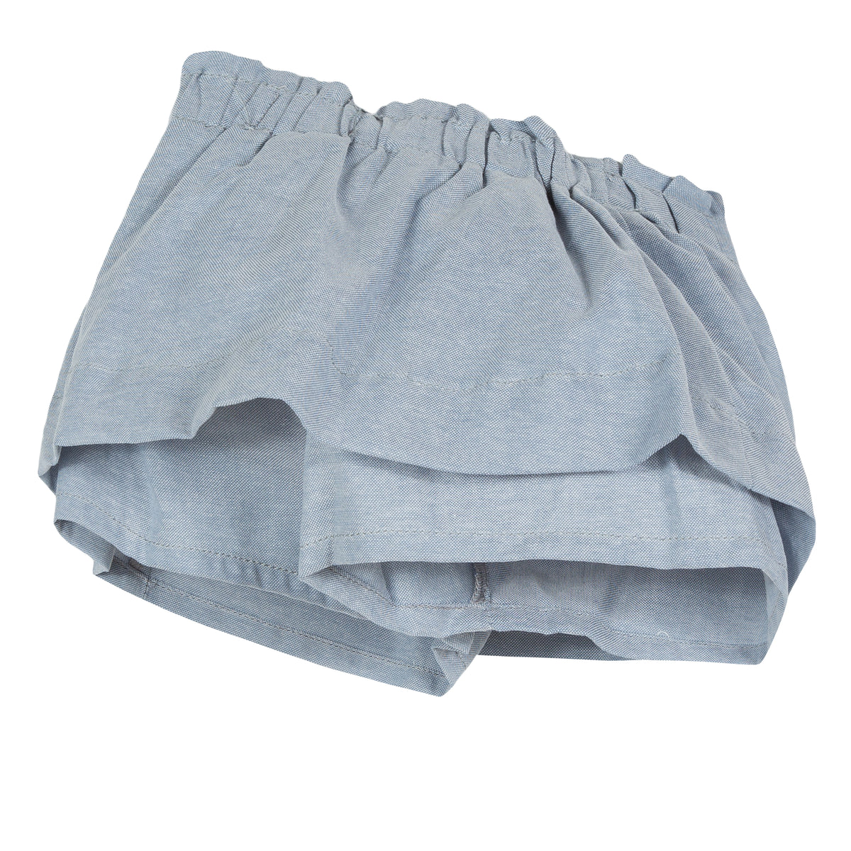 Light blue chambray skort is animated with elegant flat pleats on the waist, bringing a puffing effect to the silhouette. Designed by Jean Bourget.