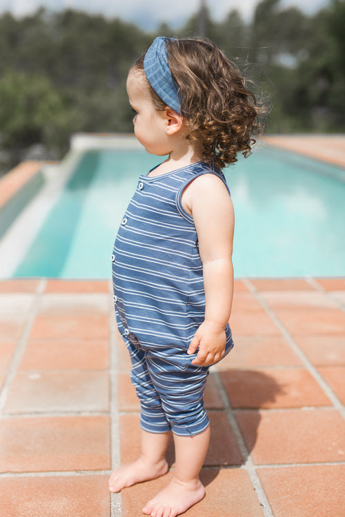 Little girl standing by a pool barefoot wearing blue and white striped sleeveless overalls by 1+ In The Family.