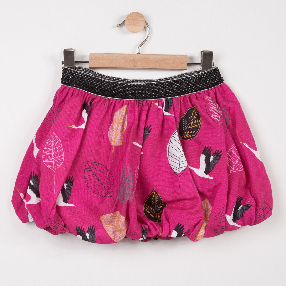 Catimini short bubble skirt in fuchsia with a stork print on a crepe lined bottom and elastic waistband.