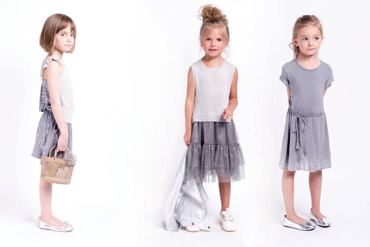 Girls sleeveless sweater dress in grey. The top has shimmer and the skirt is polyester with specs of shimmer. Designed by Imoga.
