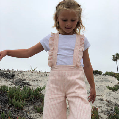 Girls blush color  high waisted overalls with ruffled straps down the back. 100% cotton. Shop Vignette today.