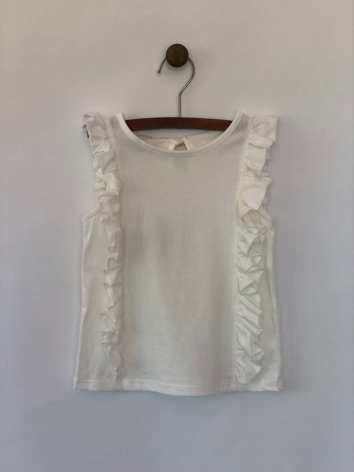 Girls sleeveless ivory tank top with ruffles lining both sides. Shop Vignette for girls.