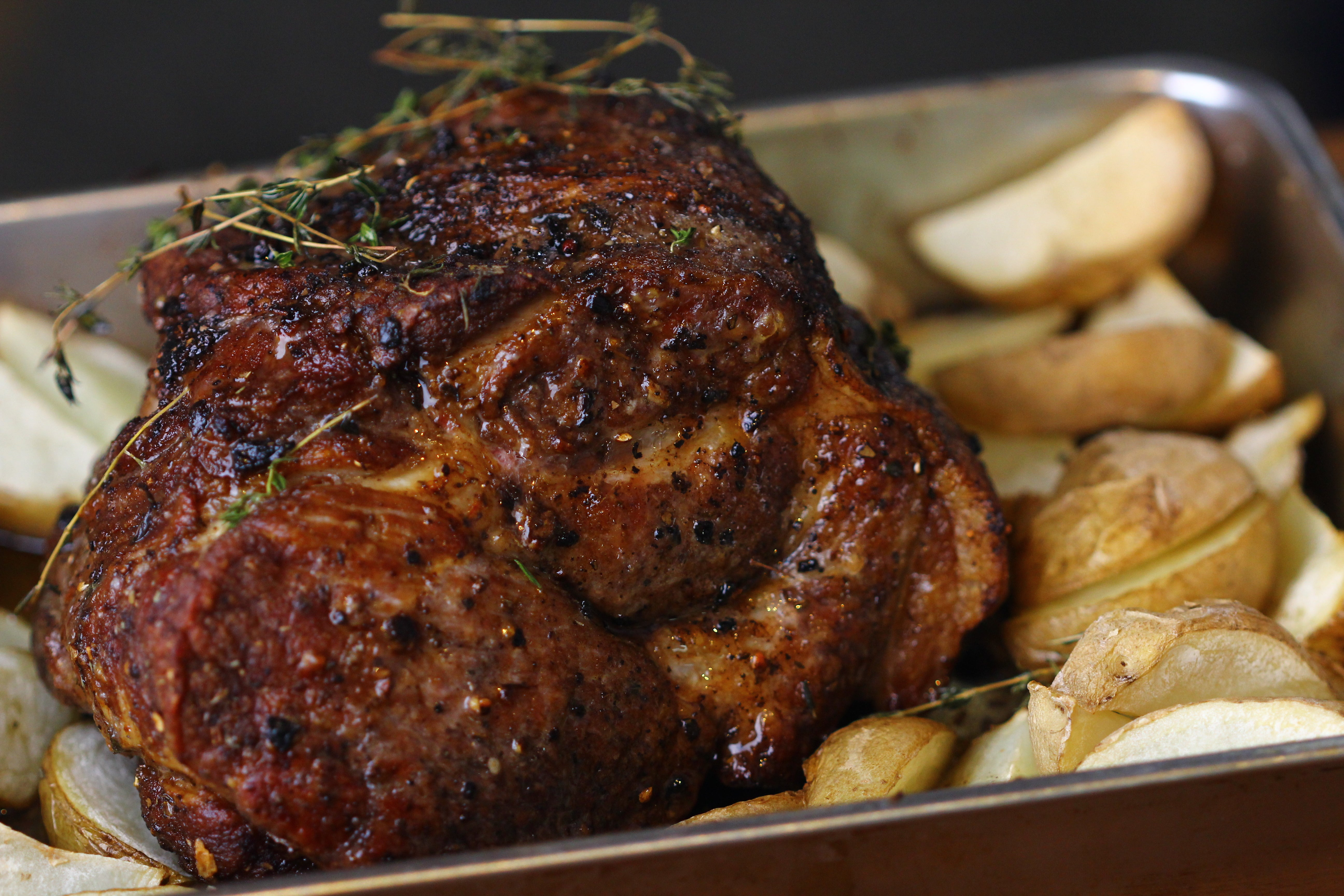 Roasted pork shoulder with its bed of potatoes and thyme