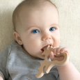 Baby holding natural wood teether in mouth