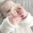 Baby holding wooden teether
