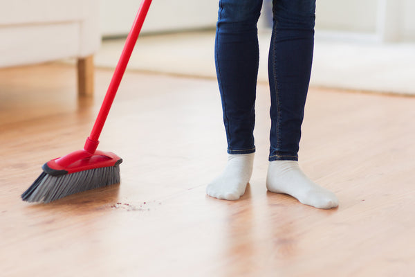 person in socks with broom