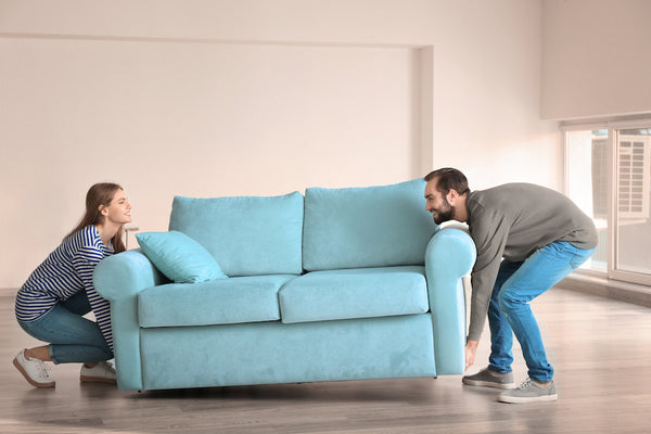 man and woman moving heavy couch