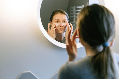 woman looking in mirror while putting skin cream under eyes