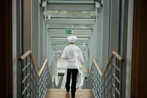 A chocolatier walking downstairs with chef hat on