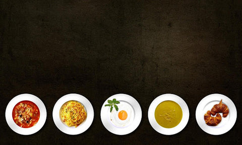 Several dinner plates lined up on black table