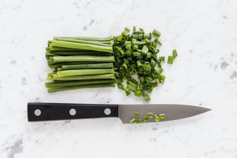 green onion and knife on top of marble counter