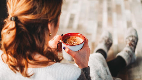 Woman holding cup of hot chocolate with two hands