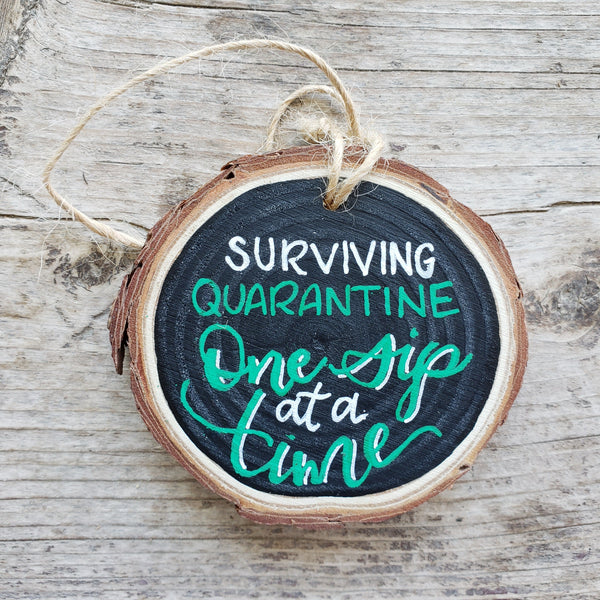 rustic wood slice ornament that says surviving quarantine one sip at at time in green and white hand lettering